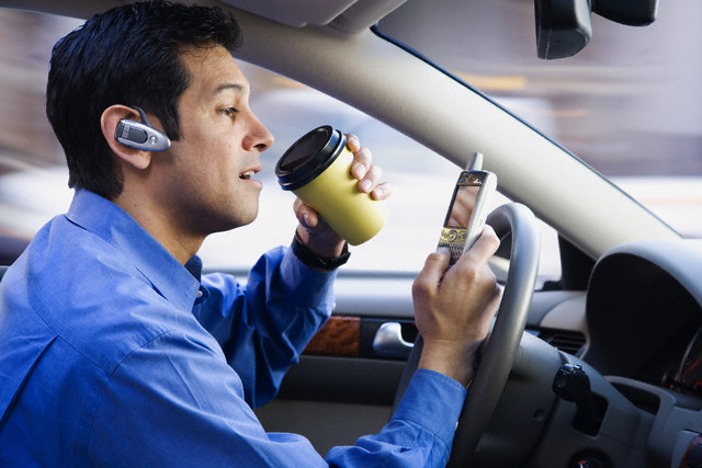 Hispanic businessman using cell phone drinking coffee and driving